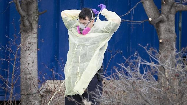 Un homme avec un masque enfile une blouse médicale.