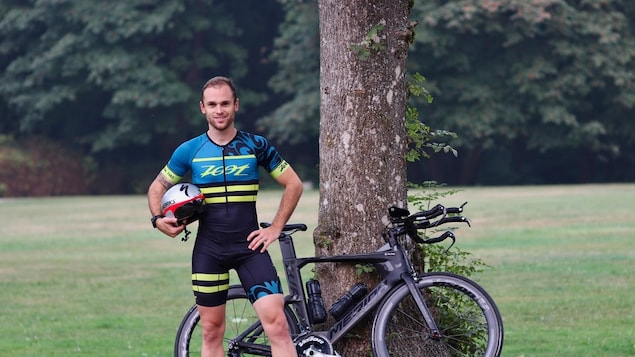 un homme en tenue de cycliste devant un vélo, le casque à la main.