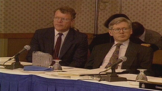 Deux hommes assis devant des microphones, à une table de négociation