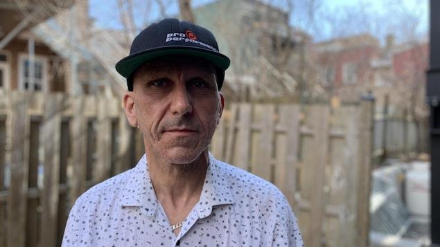 Un homme debout avec une casquette