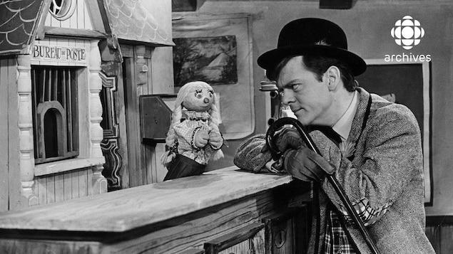 Devant le bureau de poste, Bobinette, debout derrière le comptoir, discute avec le personnage de Bobino qui y est appuyé.