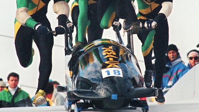 27 février 1988 aux Jeux olympiques de Calgary. Le pilote de l'équipe bobsleigh à quatre masculine de la Jamaïque Dudley Stokes saute dans son engin alors que ses coéquipiers poursuivent la poussée de départ. (Photo: GEORGES GOBET/AFP/Getty Images)
