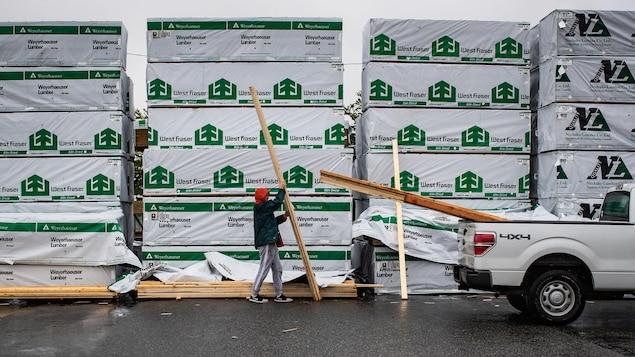 Un homme charge du bois dans une camionnette devant des palettes de 2x4.