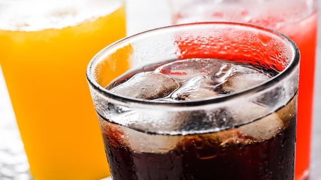 Des verres de cola et de jus de fruits vus de près.