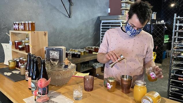 Un homme portant un masque et préparant un cocktail.