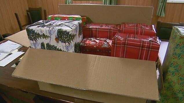 Boîtes de cadeaux dans un carton sur une table.