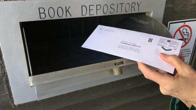 Une main dépose un bulletin de vote dans la boîte de dépôt de Whitehorse au Yukon.