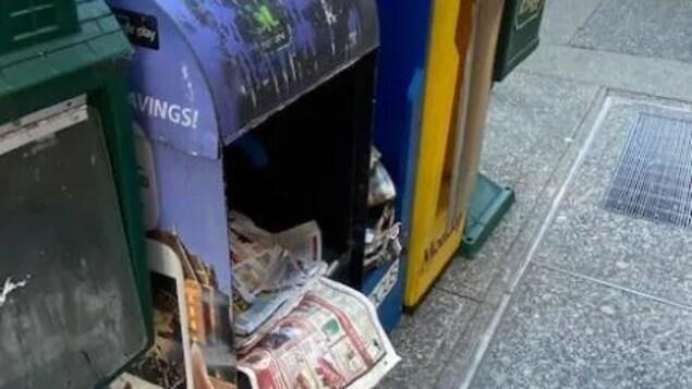 Cinq boîtes de journaux sur un trottoir. Elles sont sales. L'une d'elles n'a plus de porte et des journaux sont éparpillés à l'intérieur de la boîte.