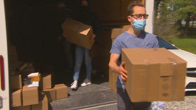 Un homme porte une boîte.