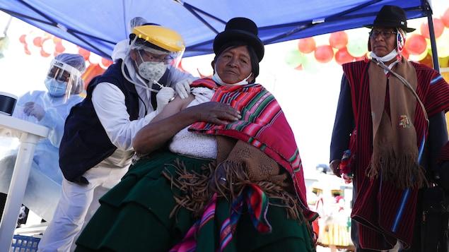 Une femme vêtue d'un habit traditionnel se fait injecter le vaccin.