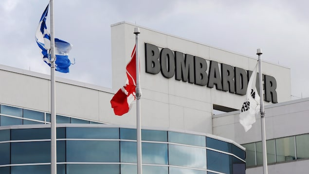 Des drapeaux aux couleurs de Bombardier, du Québec et du Canada.