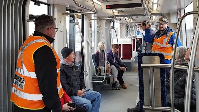 Des gens assis et debout dans un wagon de métro.