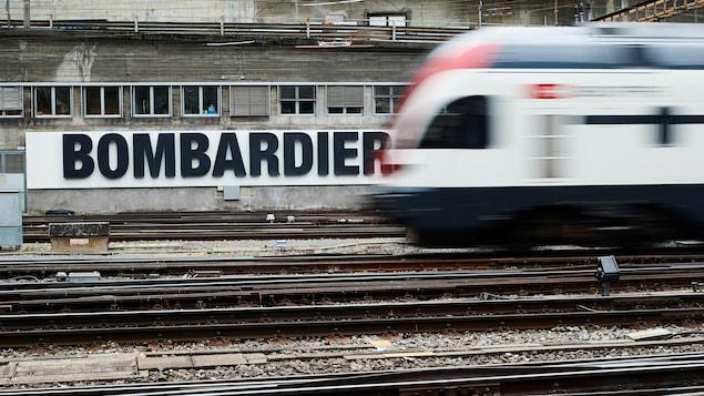 Un train suisse passe devant une publicité de Bombardier placardée sur un mur d'une gare de Berne, en Suisse.
