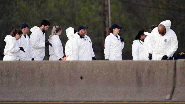 Des policiers en combinaison blanche sur la route.