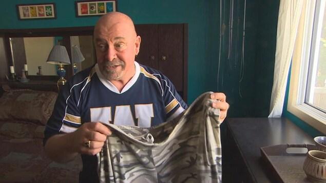 Un homme vêtu d'un chandail des Blue Bombers de Winnipeg tient dans ses mains un pantalon.