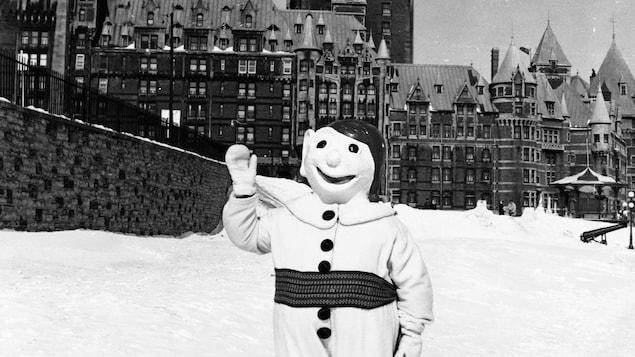 La mascotte se tient debout sur un sol enneigé, le Château Frontenac en arrière-plan.