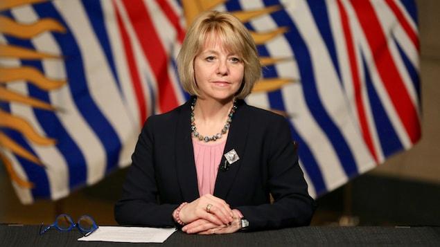 Bonnie Henry en conférence de presse, devant le drapeau de la Colombie-Britannique.