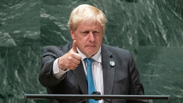 Boris Johnson, l'air sérieux, lève le pouce.