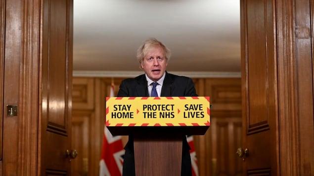 Boris Johnson se tient derrière un lutrin sur lequel on peut lire : « Restez à la maison, protégez le NHS (réseau de la santé), sauvez des vies. »