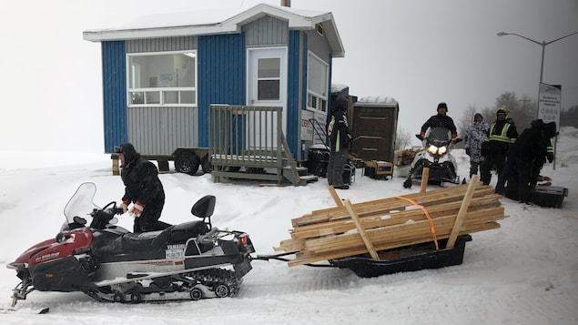 Une personne transporte des planches à l'aide d'une motoneige.
