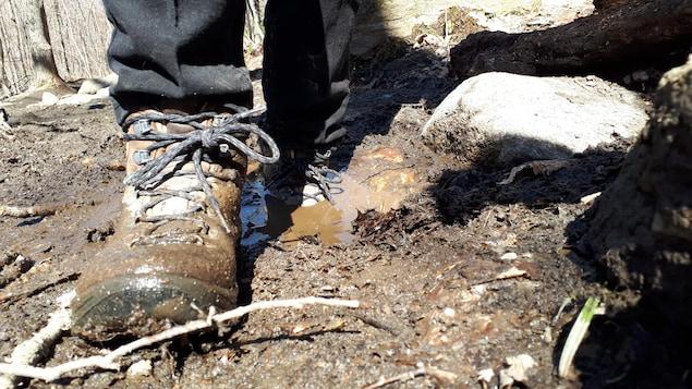 Un randonneur marche dans de la boue