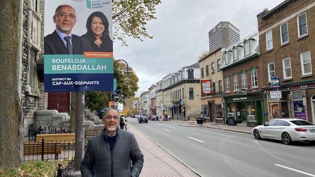 رجل يقف أمام لافتة انتخابية معلقة على عمود في الشارع.