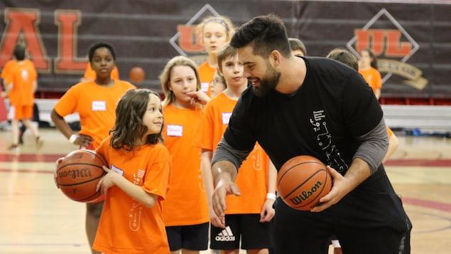 Laurent Duvernay-Tardif et un jeune participant jouent au basketball