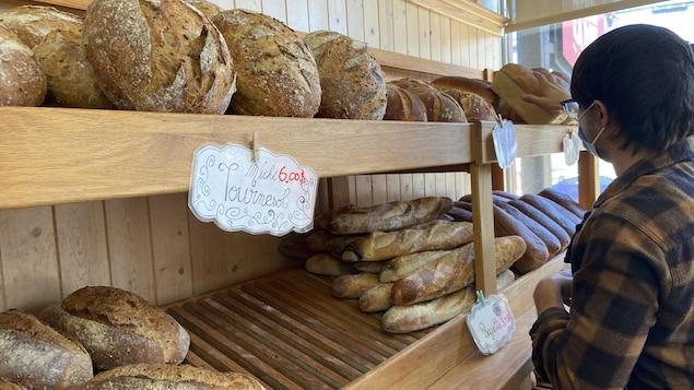 Un boulanger dispose des pains sur une étagère.