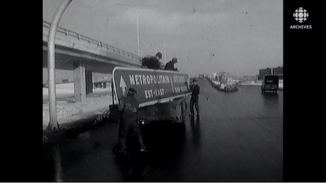 Des ouvriers installent un panneau de signalisation routière sur le boulevard Métropolitain en 1963.