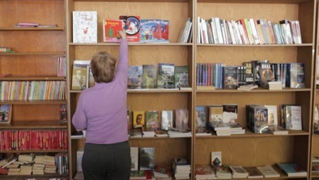 Une femme place un livre sur une étagère.