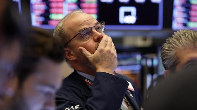 Un courtier à la Bourse de New York regarde les tableaux avec la main droite sur sa bouche.