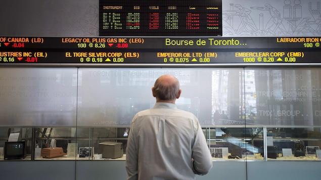 Un homme regarde défiler sur un panneau lumineux les cotes boursières.