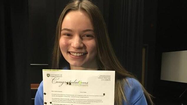 Une jeune femme pose fièrement avec un document la félicitant.