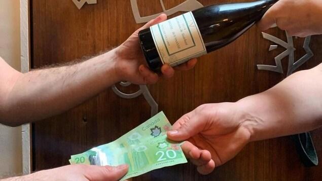 Quelqu'un donnant une bouteille de vin et recevant des billets de banque.