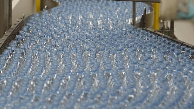 Plusieurs centaines de bouteilles de plastique vides défilent sur un tapis roulant dans une usine de Coca-Cola.
