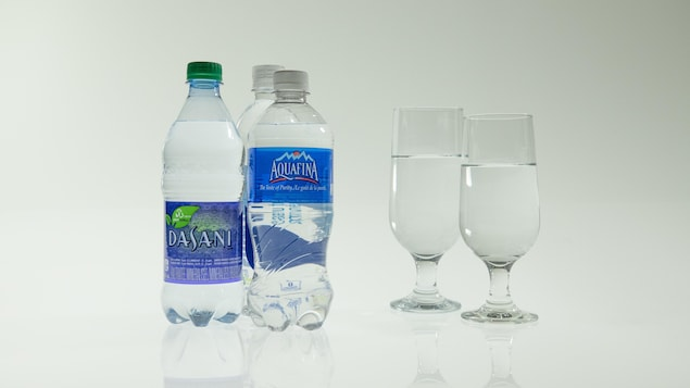 Trois bouteilles d'eau et deux verres d'eau.