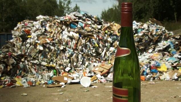 Une bouteille de verre devant une montagne d'objet à recycler.