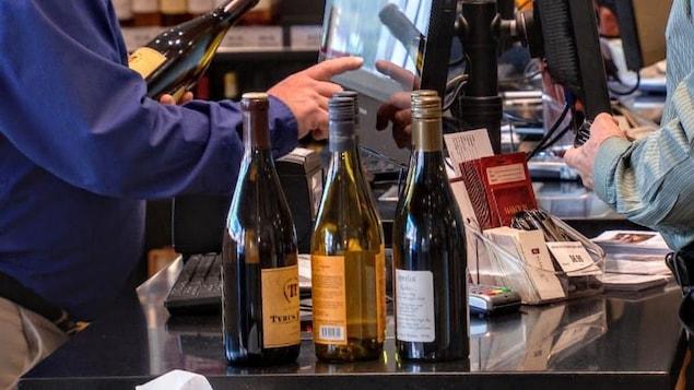 Achat de bouteilles de vin dans un magasin de vente d'alcool.