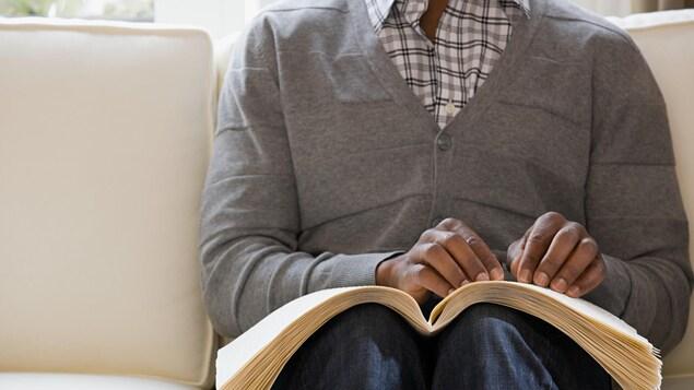 Un homme aveugle lit un livre écrit en braille.