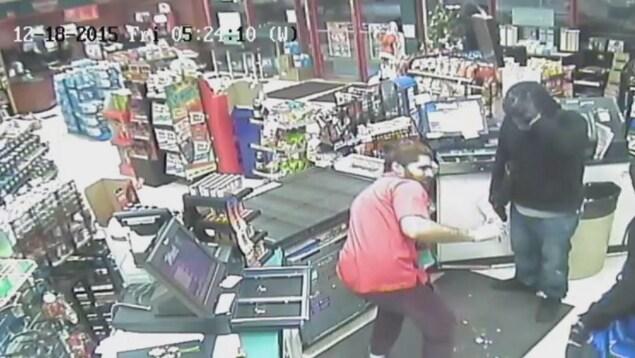 Un employé de dépanneur peine à ouvrir un coffre-fort situé sous le comptoir de la caisse sous le regard des présumés voleurs.