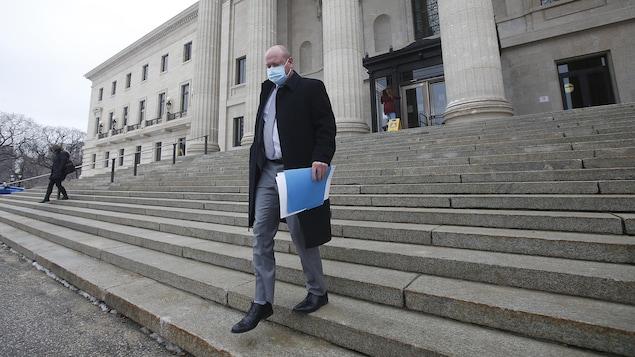 Brent Roussin descend les marches de l'escalier du Palais législatif.