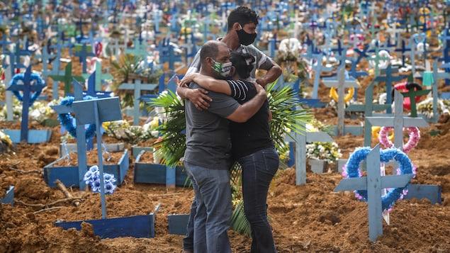 Deux personnes se serrent dans leurs bras, pendant qu'un autre regarde le nombre impressionnant de croix plantées dans le sol qui l'entourent.