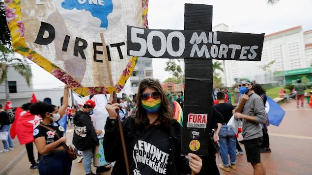Manifestante portant une affiche indiquant 500 000 morts, ce qui représente les décès liés à la COVID-19.