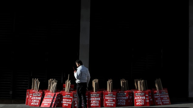 Un manifestant se tient à côté d'affiches à distribuer dans le cadre de la manifestation anti-Brexit de samedi, dans le centre de Londres.