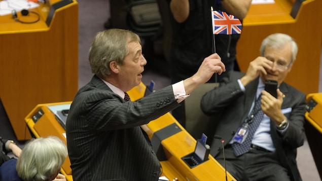Un homme brandit un petit drapeau britannique au parlement européen.