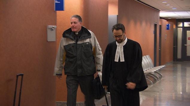 Brian Boucher et un avocat dans un corridor du Palais de justice