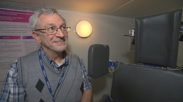 Un homme regarde la caméra en souriant. Il se tient près d'un fauteuil utilisé pour effectuer le test dont il parle.