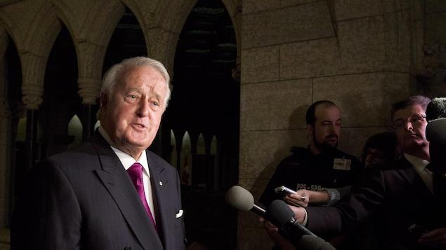 L'ancien premier ministre Brian Mulroney répond aux questions des journalistes à la sortie du cabinet libéral jeudi.