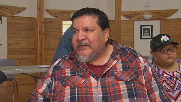 Un homme autochtone porte une chemise à carreaux.