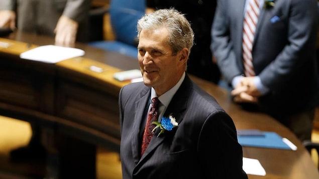Brian Pallister est debout et souriant dans la Chambre de l'assemblée. On voit des députés également debout en arrière-plan.